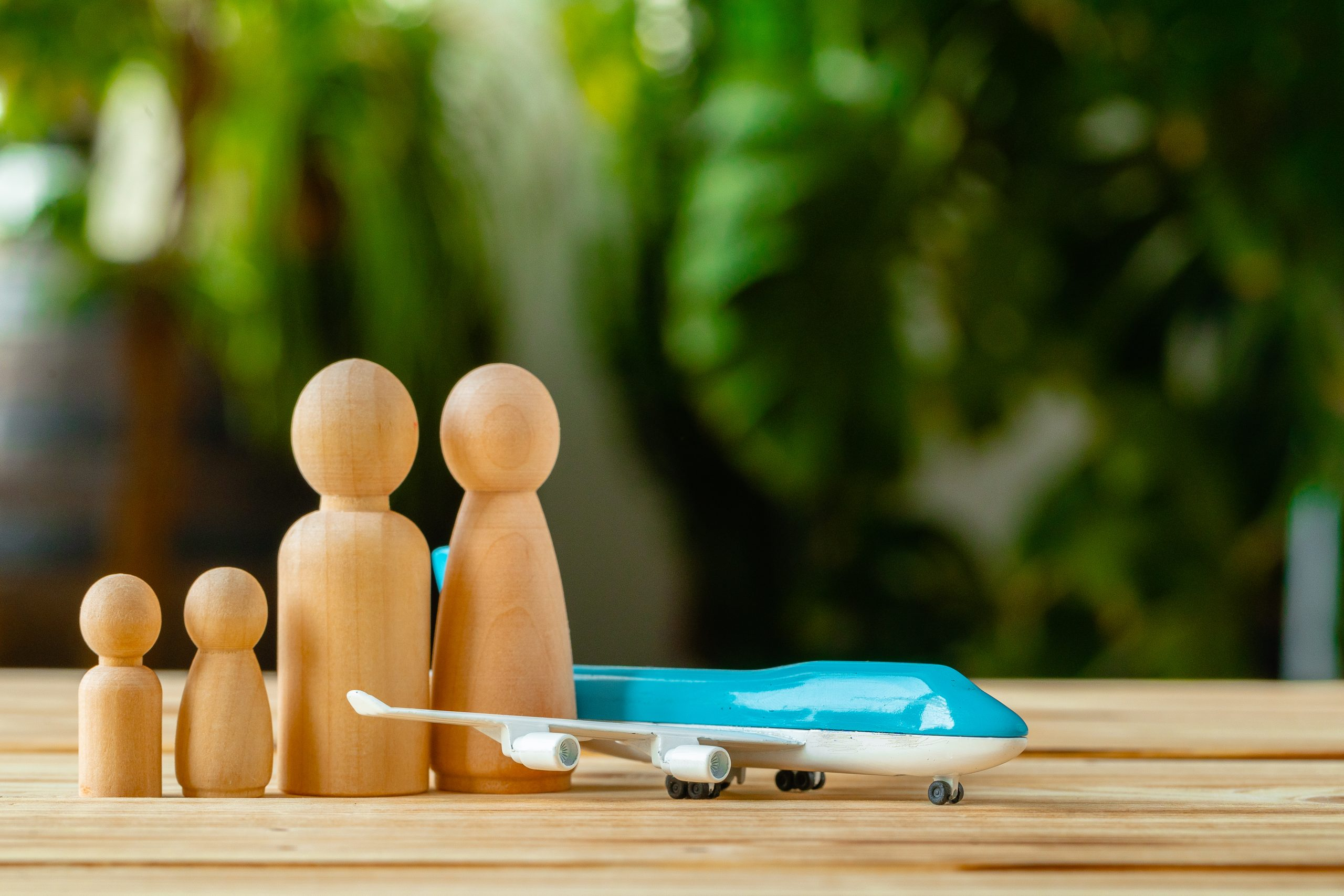 Family travel and vacation concept. Wooden figures of family and toy plane